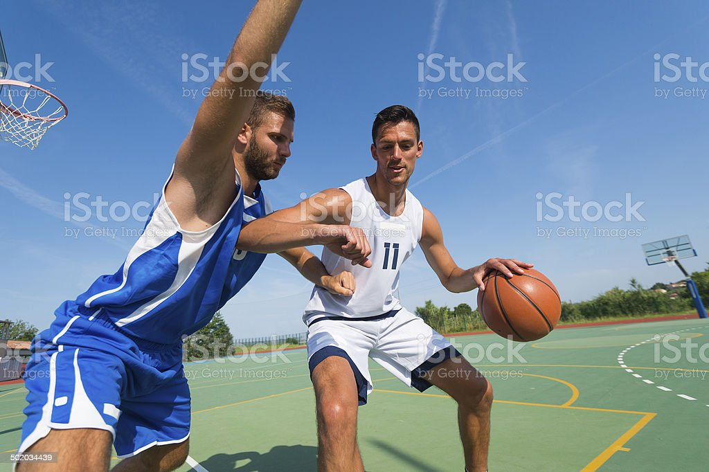 Basketball players in dribbling action stock photo