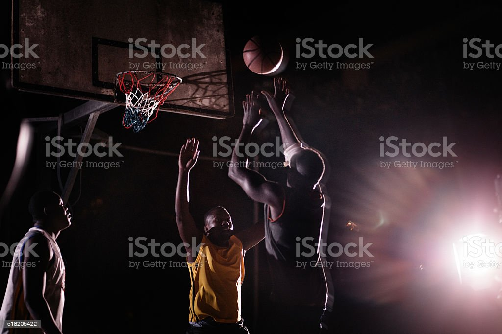 Basketball Players Playing in Court During Nighttime stock photo