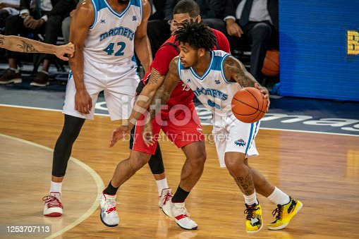 Basketball player in white jersey holding ball while player in red jersey blocking him during the match.