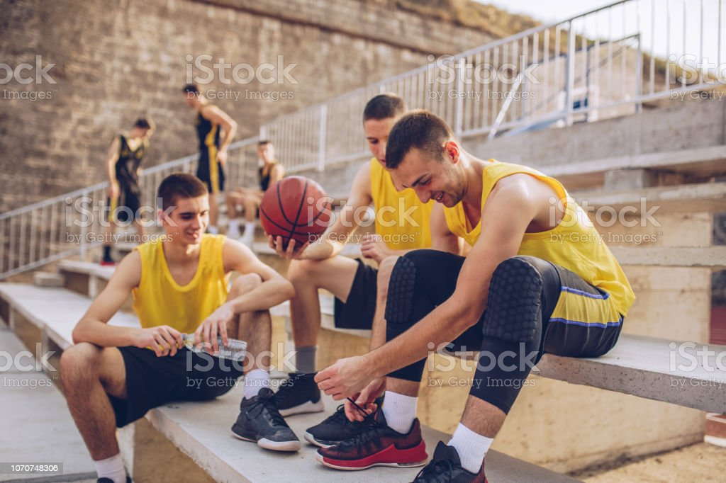 Group of male basketball players relaxing after playing basketball