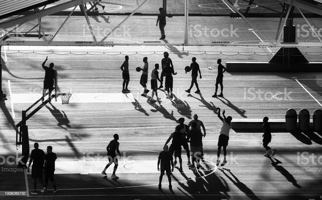 Basketball players silhouettes at sunset, New York City. stock photo