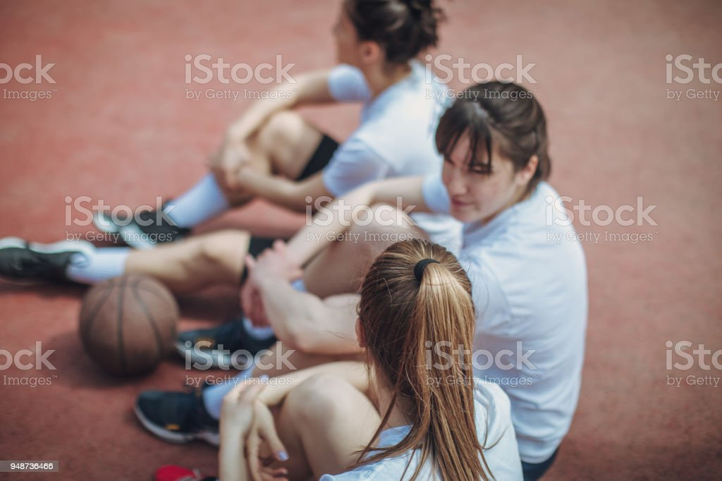 Basketball players sitting on the court stock photo