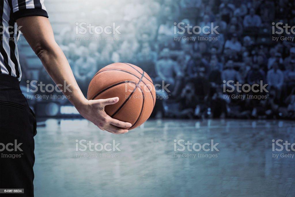 Árbitro de basquete segurando uma bola num jogo de basquetebol durante um tempo limite - foto de acervo