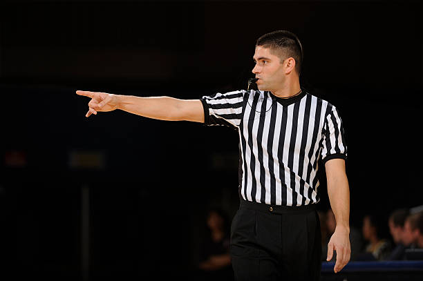 Basketball Referee A basketball referee makes call during a game. referee stock pictures, royalty-free photos & images