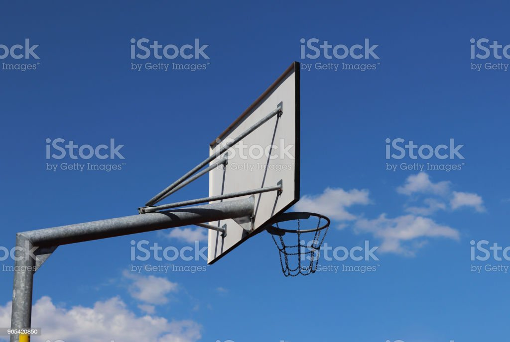 Basketball ring with a basket of chains against the blue sky. zbiór zdjęć royalty-free