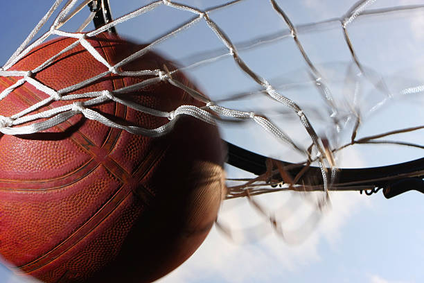 Basketball scoring points through the net stock photo