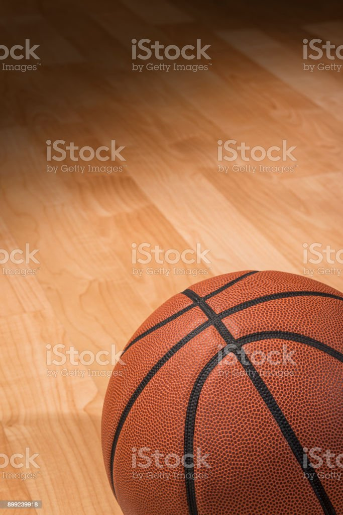 Basketball sitting in the spotlight on a court stock photo
