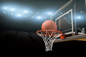 A basketball going through a basketball goal mid air in  professional basketball stadium or arena with stadium lights and flares and copy space for text.