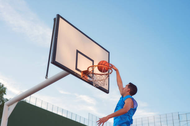 Basketball street player making a slam dunk Basketball street player making a slam dunk slam dunk stock pictures, royalty-free photos & images