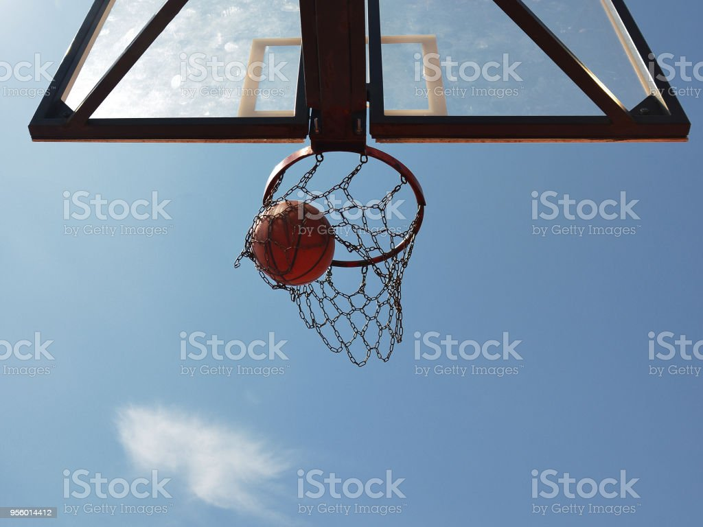Basketball swishes through the hoop looking from below stock photo
