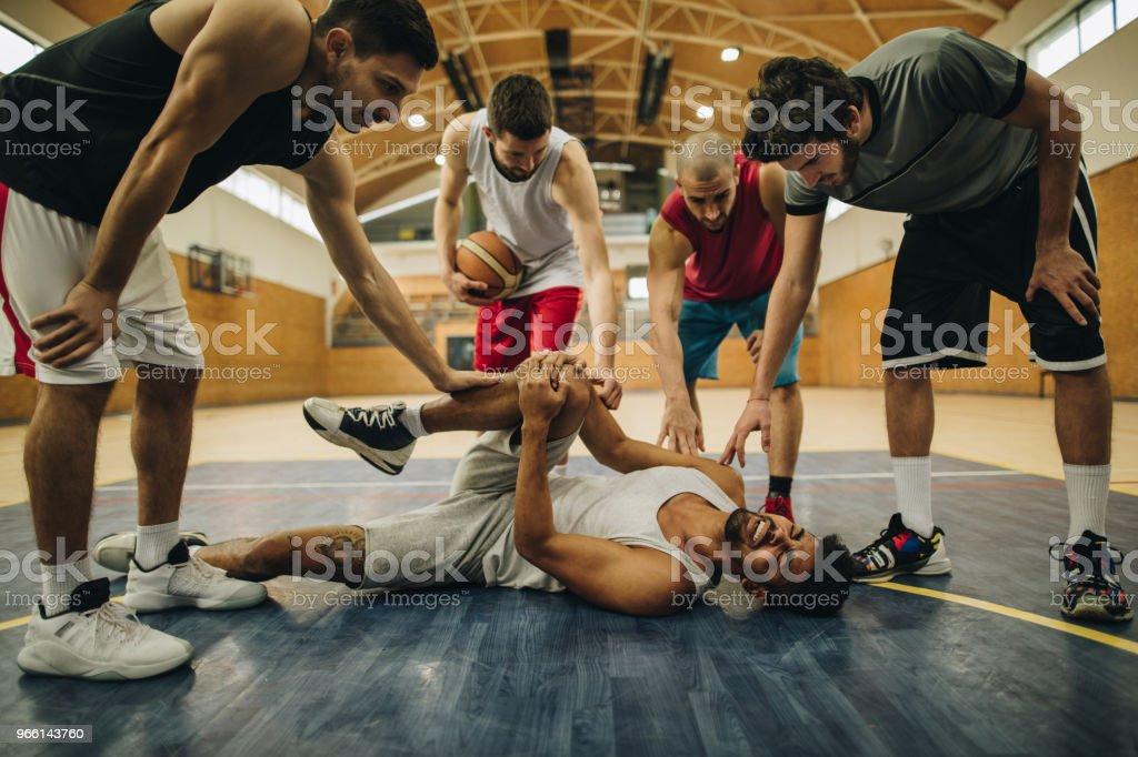 Basketlag stödja deras skadade lagkamrat på domstolen. - Royaltyfri Afroamerikanskt ursprung Bildbanksbilder
