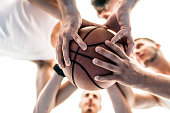 Photo of Three basketball men holding ball in hands during summer day outside. Three Caucasian Friends Stacking Hands presenting unity outdoors.