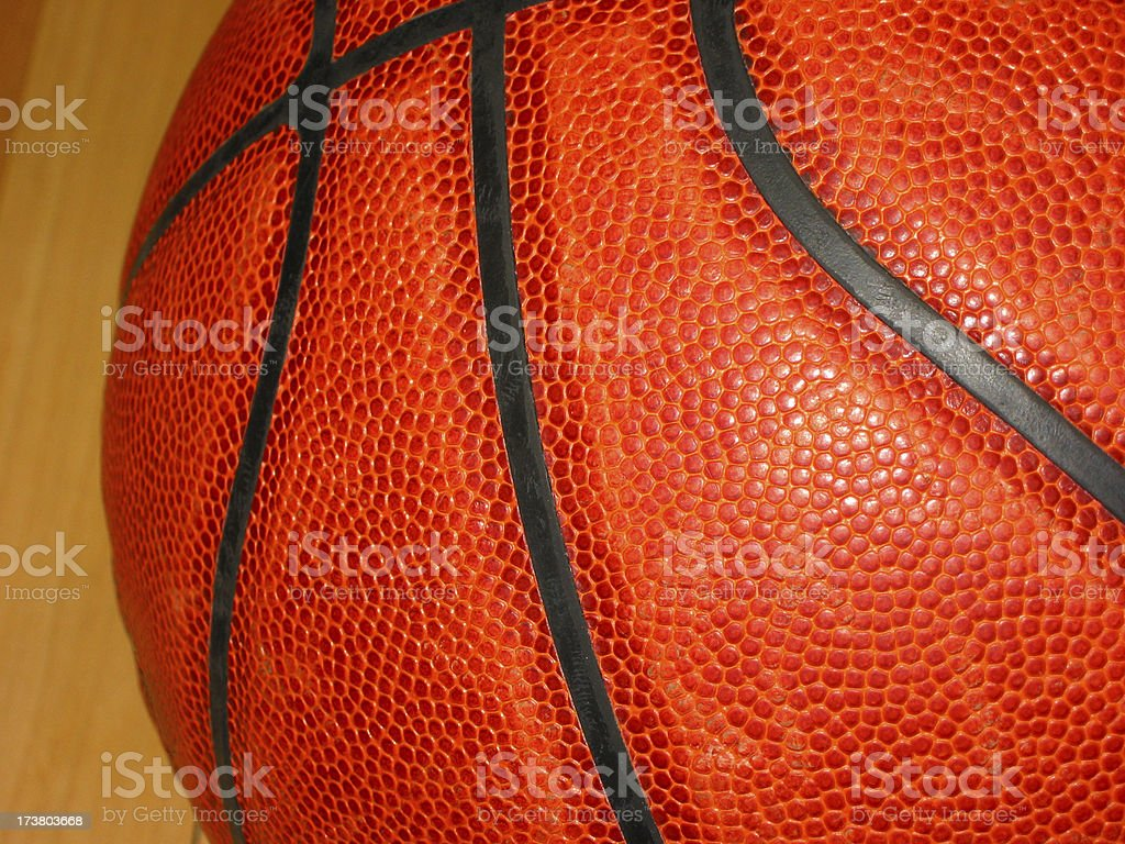 Close view of a very orange basketball against a wood court.