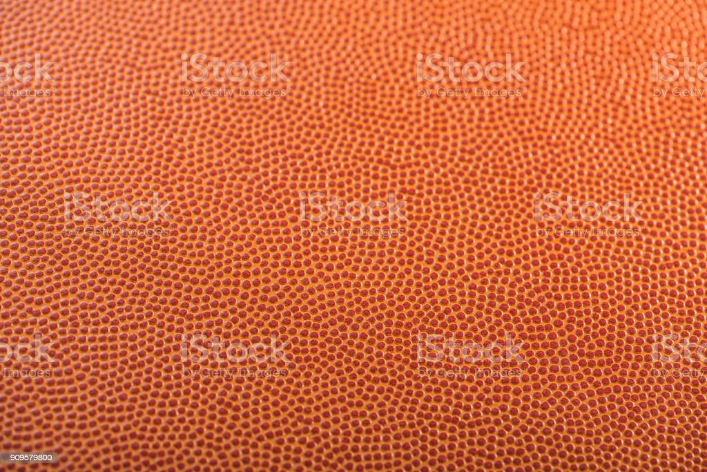 A close-up with selective focus on a basketball\'s pebbled textured.