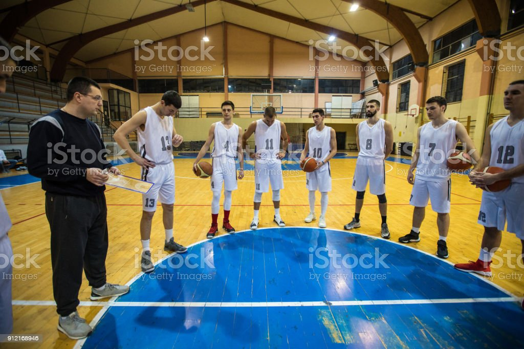 Basketball coach advising his players during practice