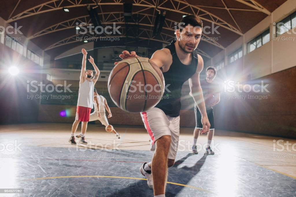 Young basketball player leading the ball on a sports training with...