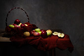 Basketful of various type of apple with some on the wooden table and one of them is cut in to half