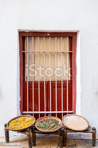 baskets outside a window with seeds herbs and spices drying in the bright outdoor sunlight