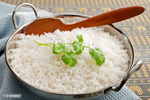 Basmati rice in a steel karahi, garnished with coriander,with a wooden spoon.