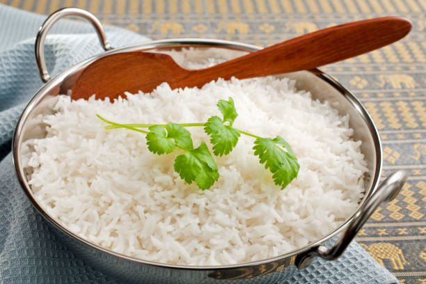 Basmati Rice with Coriander in a Balti Dish Basmati rice in a steel karahi, garnished with coriander,with a wooden spoon. balti dish stock pictures, royalty-free photos & images