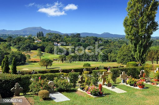On a lush countryside background, a cemetery with ancient disk-shaped tombs depicting the country.