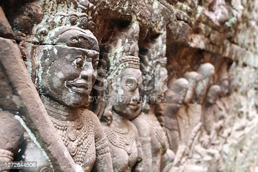 Bas-relief on the Hidden Wall of Terrace of the Leper King. Carvings of Apsara dancers and guardians of underworld, Angkor Wat (Angkor Thom), Siem reap, Cambodia. Focus on the figure in the foreground
