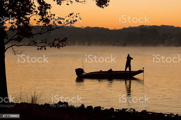 Silhouette of bass fisherman in the early light of dawn.  Mist over the lake, pre-sunrise.  Taken in the Autumn on Lake Wylie.