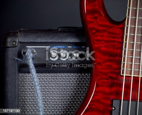 An electric bass guitar leaning against a guitar amplifier. Focus is on the knobs of the amp.  Black background.