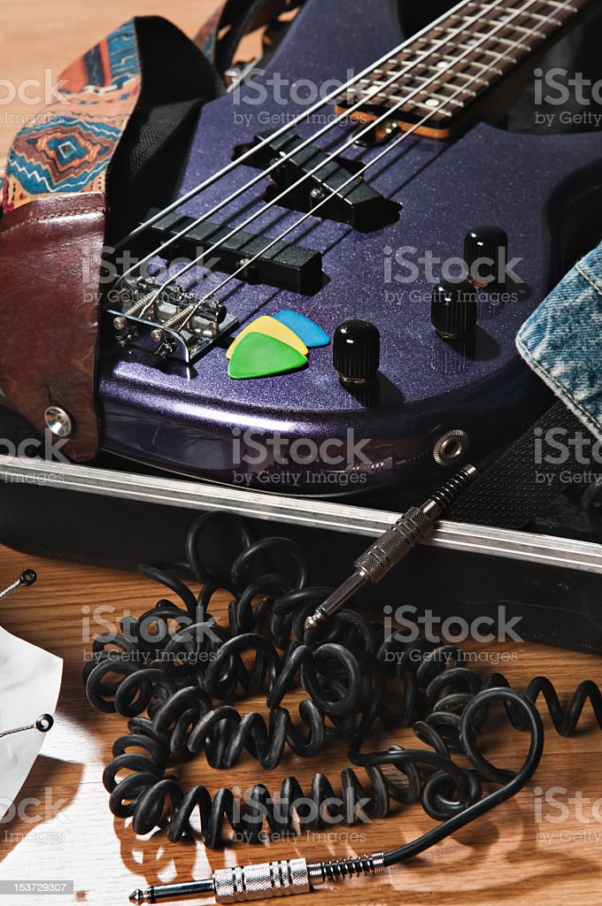 Bass guitar on case with pick royalty-free stock photo