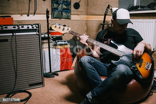 849362192 istock photo Bass guitarist playing guitar in music studio 842747546
