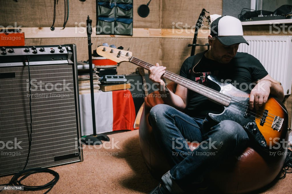 Bass guitarist playing guitar in music studio stock photo