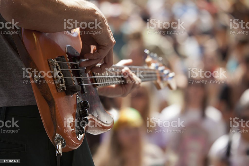 bass player in front of crowd stock photo
