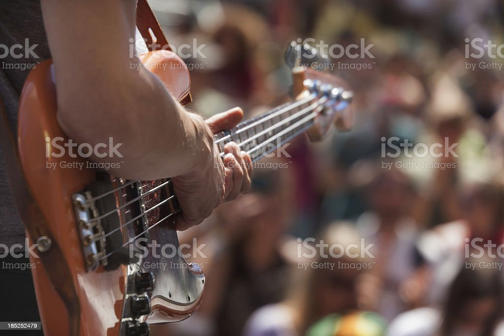 bass player infront of crowd at outdoor performance royalty-free stock photo
