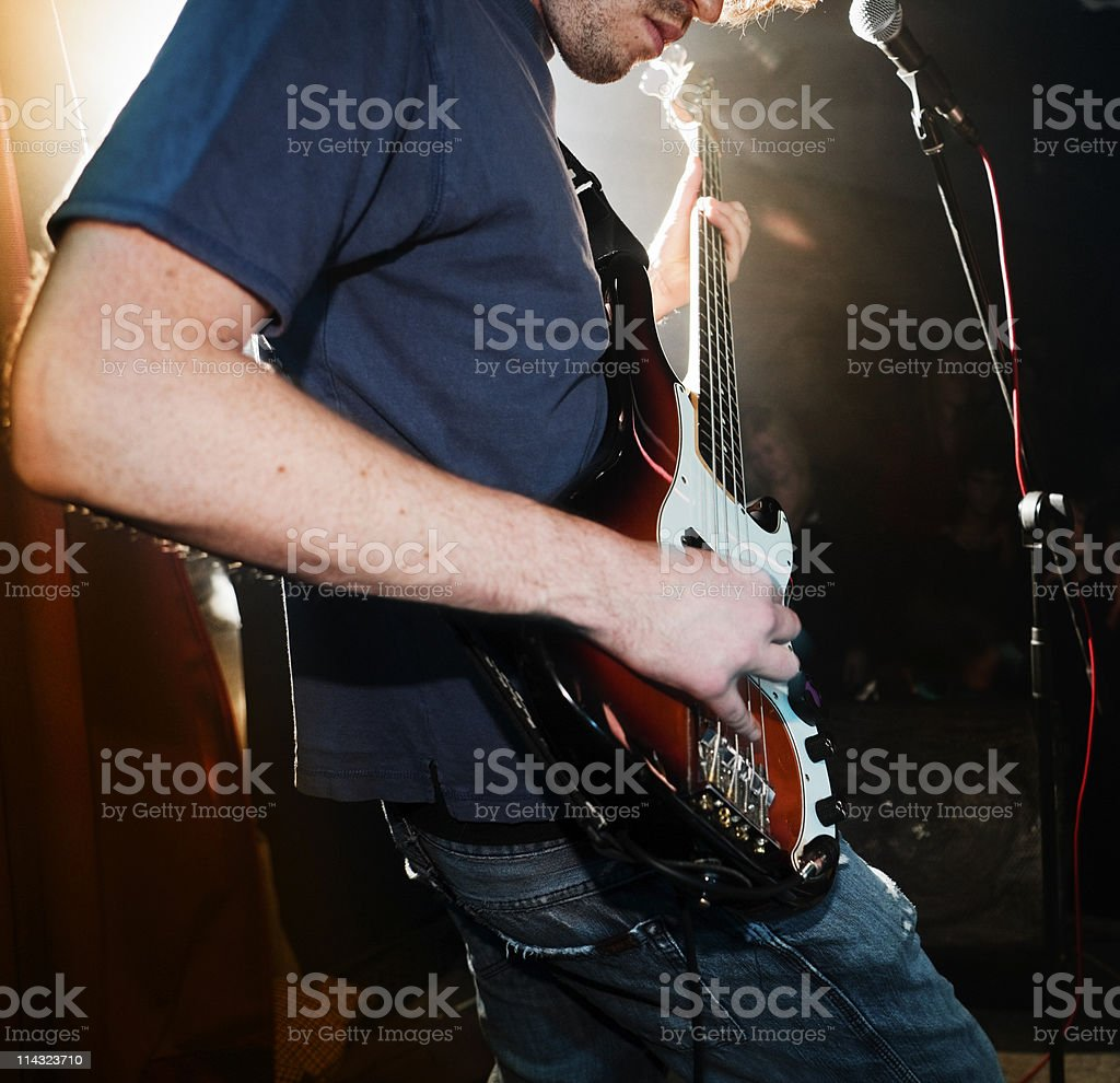 Bass player on stage with rock band stock photo