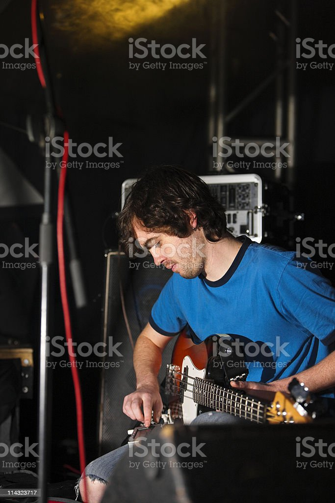 Bass player  tuning up on stage royalty-free stock photo