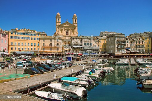 Bastia, Corsica, France - June 02, 2019: The old port (the Vieux Port), in Bastia, Corsica, France. The small port with yachts, surrounded by the medieval houses, street cafes, tiny shops, with the St. Jean Baptiste church
