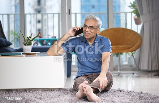 Senior man busy on phone at home