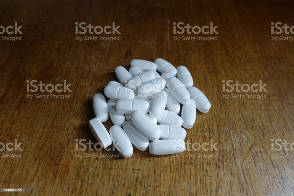 Batch of calcium citrate tablets on wooden table stock photo