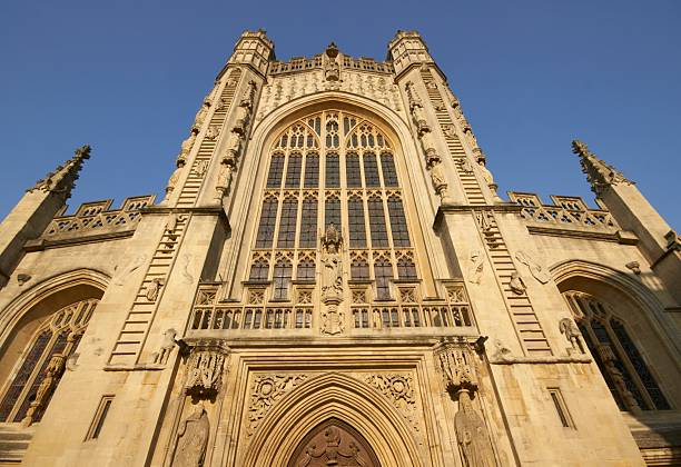 Bath Abbey West front facade of Bath Abbey. Large stain glass window set in ornately carved stone surround. 16th Century church, Bath, England, United Kingdom bath abbey stock pictures, royalty-free photos & images