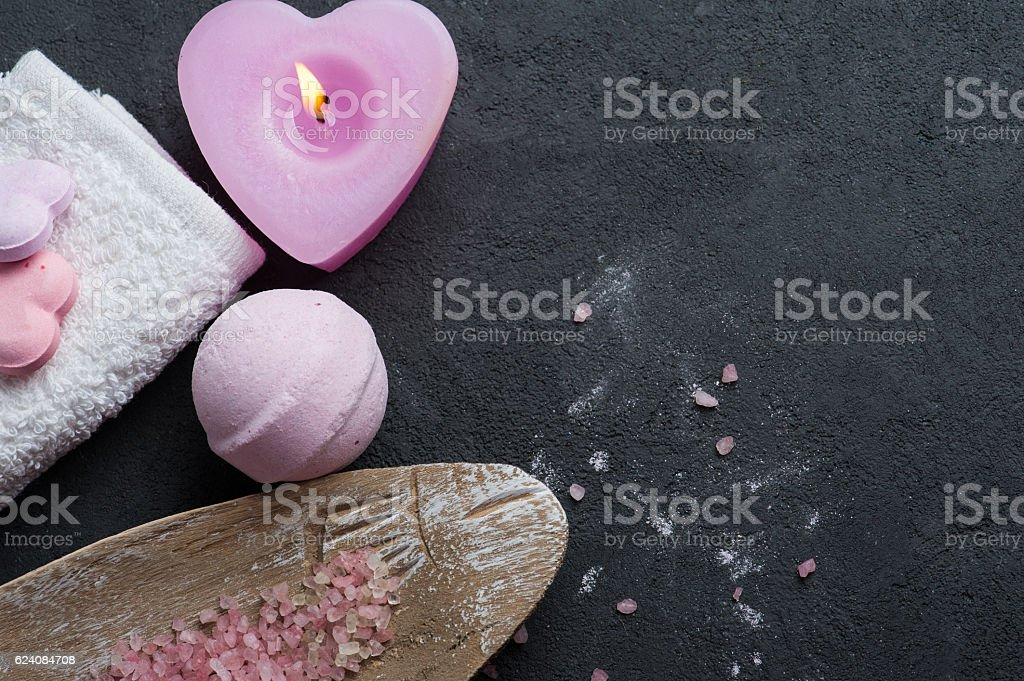 bath bomb closeup with pink lit candle stock photo