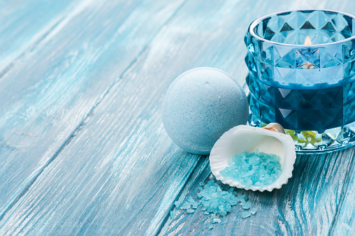 656780900 istock photo bath bombs closeup with blue lit candle 624084566