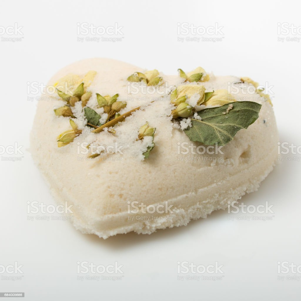 Bath bombs decorated with dried linden flowers on a white stock photo