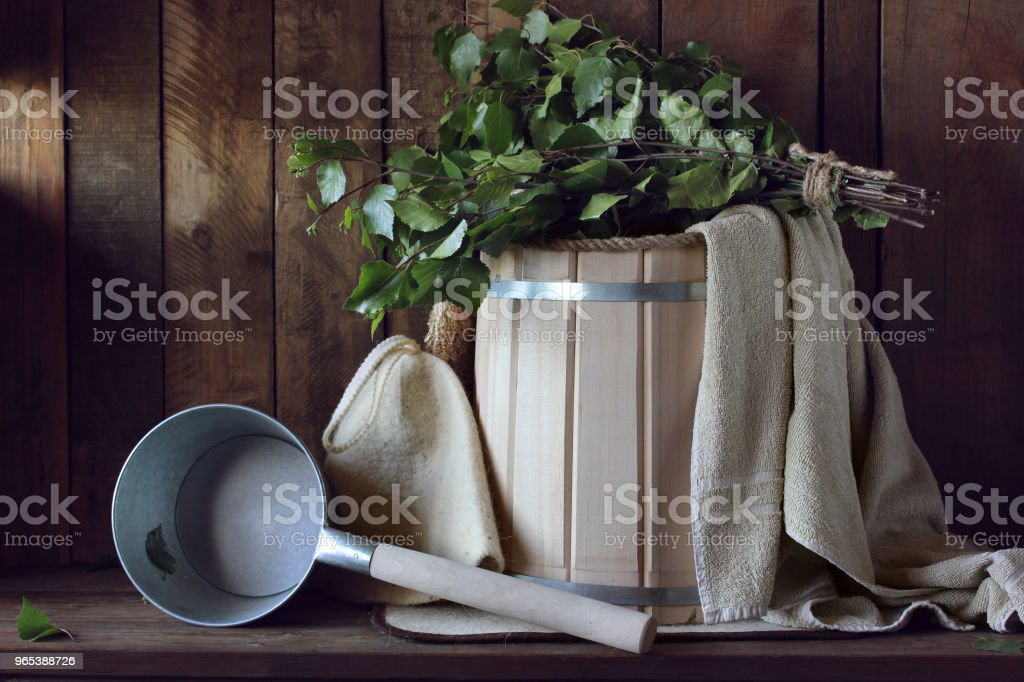 Bath broom made of birch and wooden bath bucket in a Russian bath close-up. royalty-free stock photo