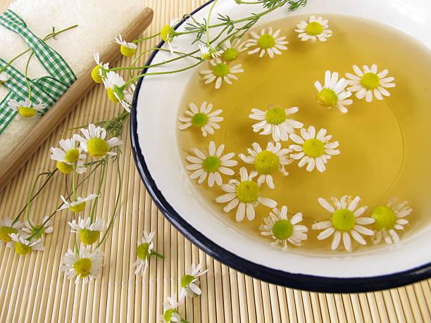 Bath essence with chamomile flowers stock photo