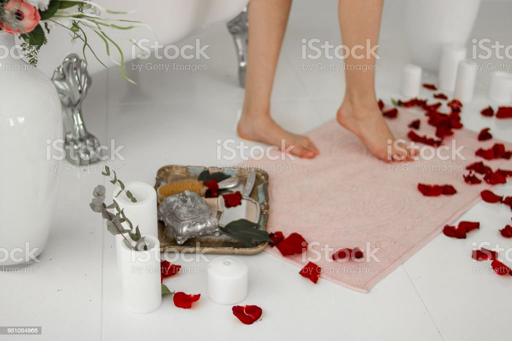 Bath mat. Legs on the rug after the bath. Rose petals and candles. stock photo