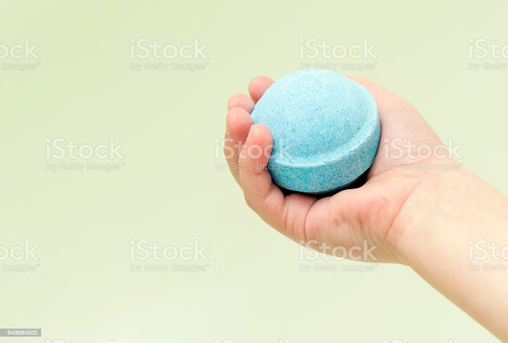 Bath or cosmetic bombs in child's hand, meant for relaxation and body care. Close-up. stock photo