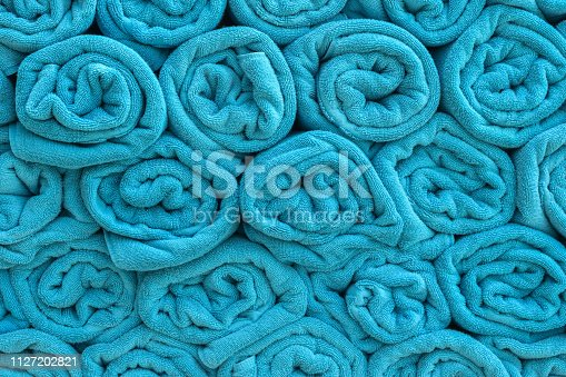 1131900491istockphoto Bath towel rolls fabric texture cloth background in blue color for swimming pool, sea beach, gym fitness in resort hotel 1127202821