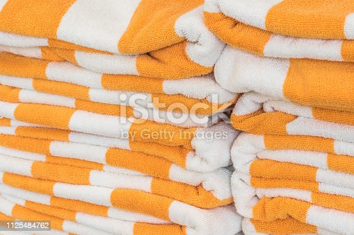 1131900491istockphoto Bath towel rolls fabric texture cloth background in white orange stripe for swimming pool, sea beach, gym fitness in resort hotel 1125484762
