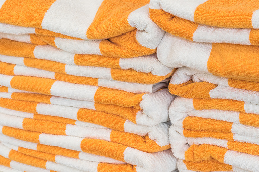 1131900491 istock photo Bath towel rolls fabric texture cloth background in white orange stripe for swimming pool, sea beach, gym fitness in resort hotel 1125484762