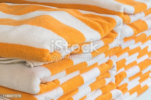 1131900491istockphoto Bath towel rolls fabric texture cloth background in white orange stripe for swimming pool, sea beach, gym fitness in resort hotel 1130377273
